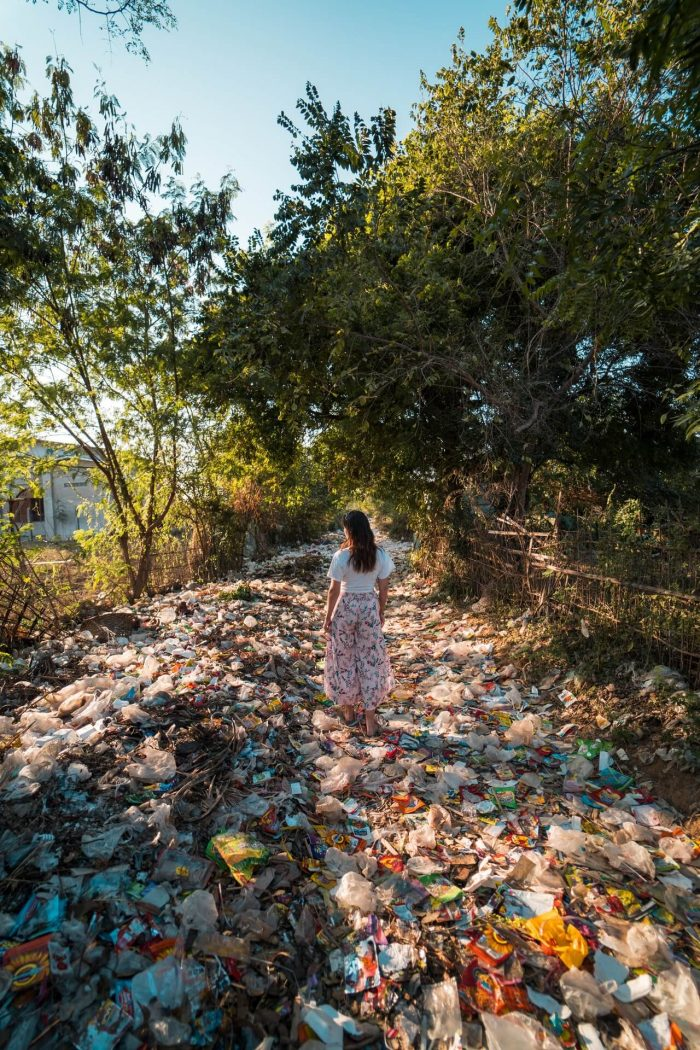 a woman standing on a pile of waste
